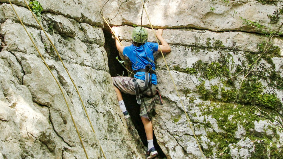 Child weaselling Ardeche rock face
